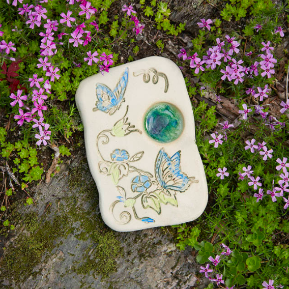 a stone with colorful butterflies carved into it with a small puddle on it nestled in a garden bed