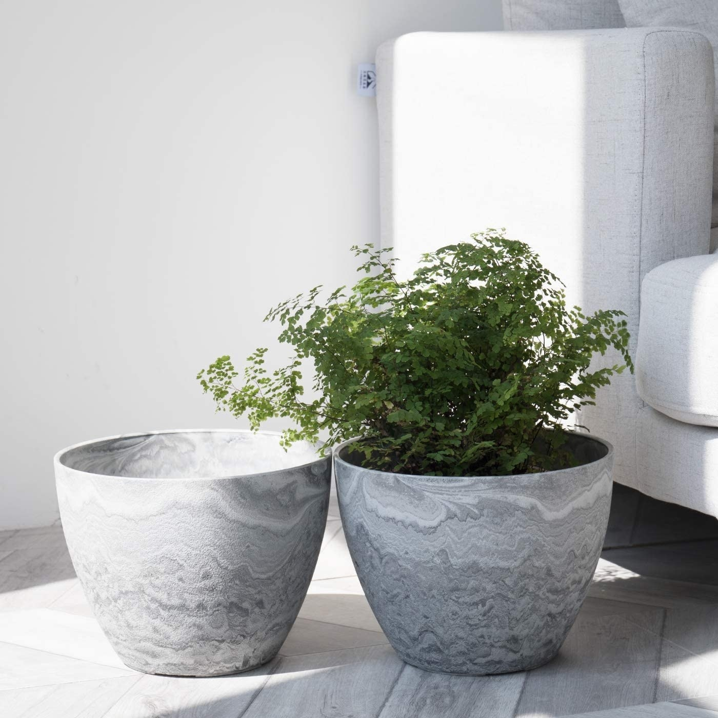 two gray planters with plants in them