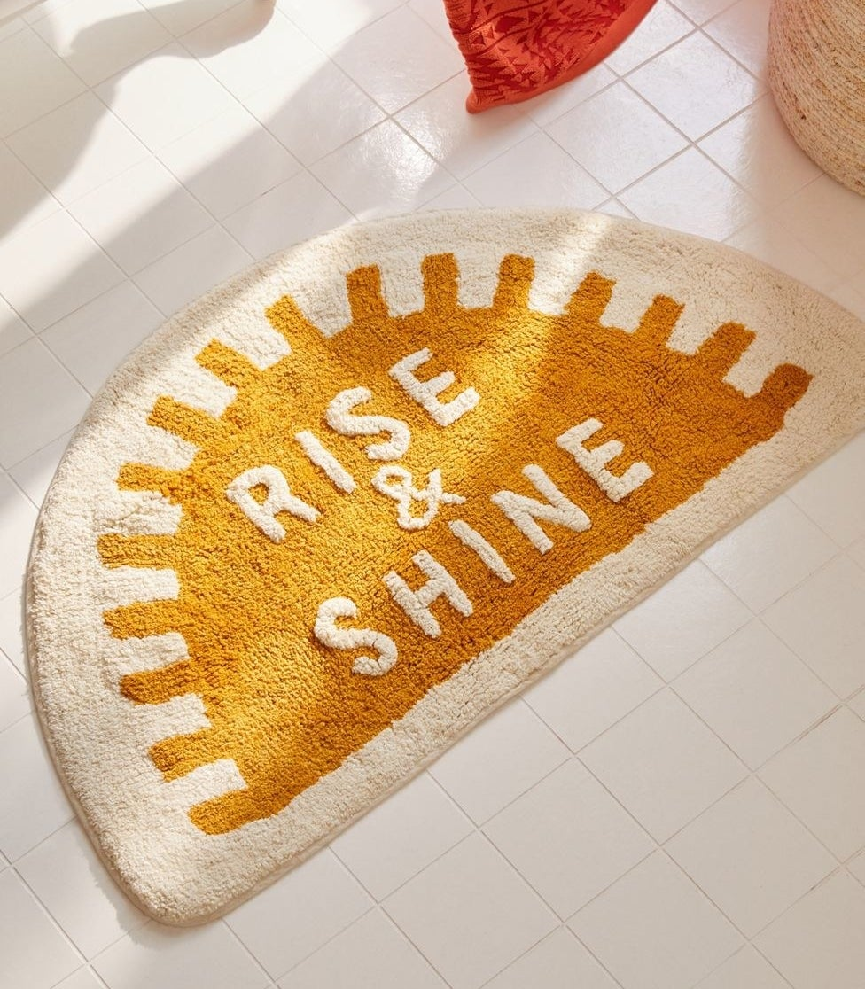 """the sun-shaped bath mat with the text """"rise & shine"""""""