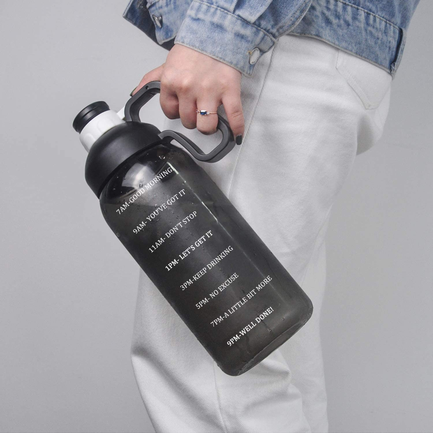 a model holding a black water bottle with inspirational text