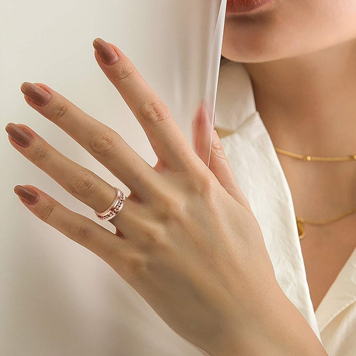 a model wearing a gold fidget spinner ring on their ring finger
