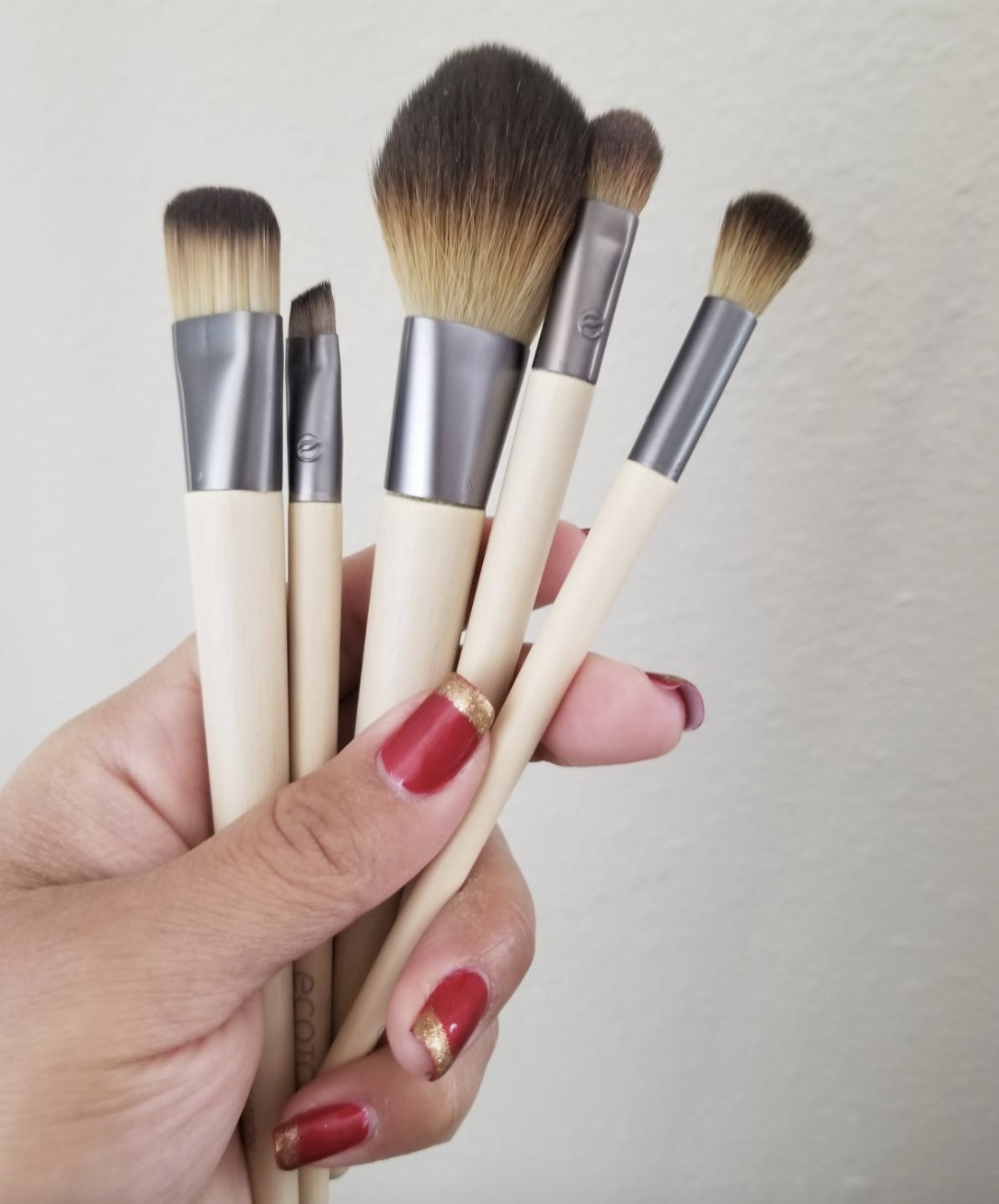 reviewer hand holding five makeup brushes