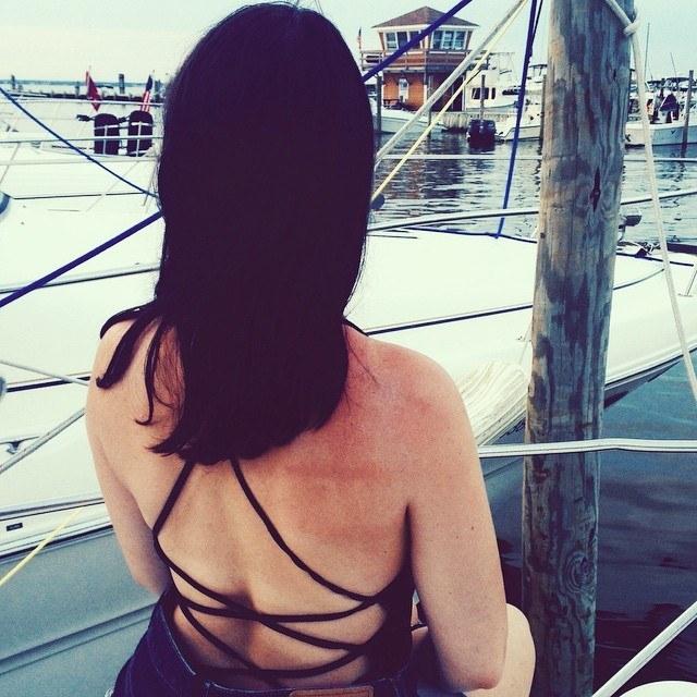 BuzzFeed Editor Emma McAnaw wearing a black dress and showcasing clear skin on their back