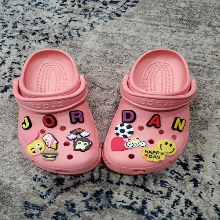 a reviewer's pink crocs covered in jibbitz