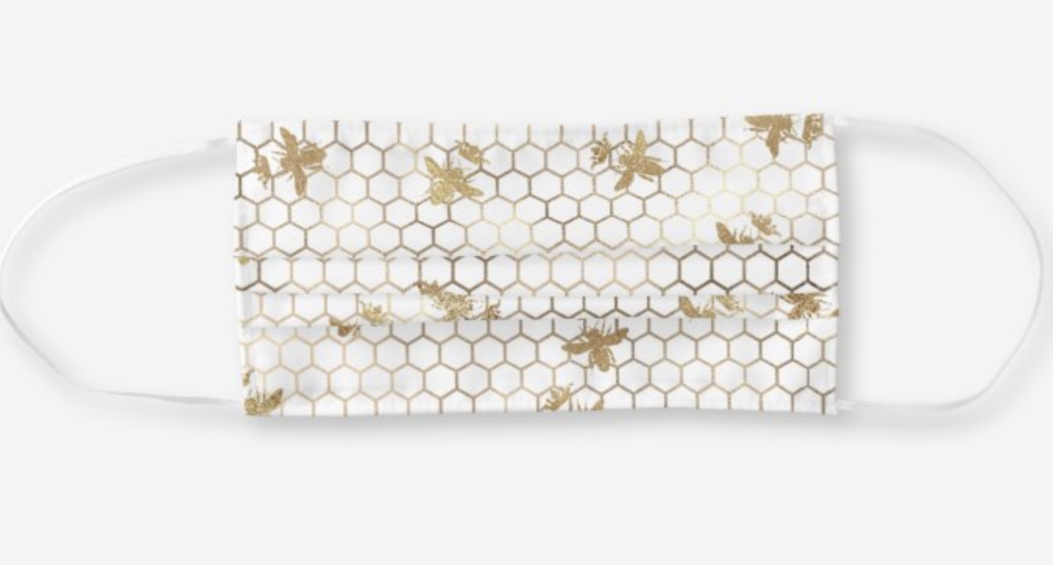 A white mask with gold honeycomb print and little gold bees