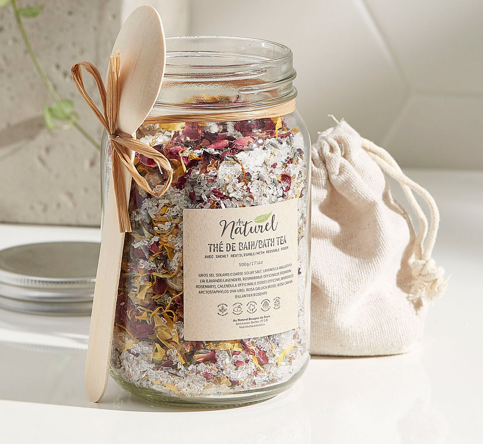 A large jar filled with bath salts There is a small wooden spoon tied around the jar with a string
