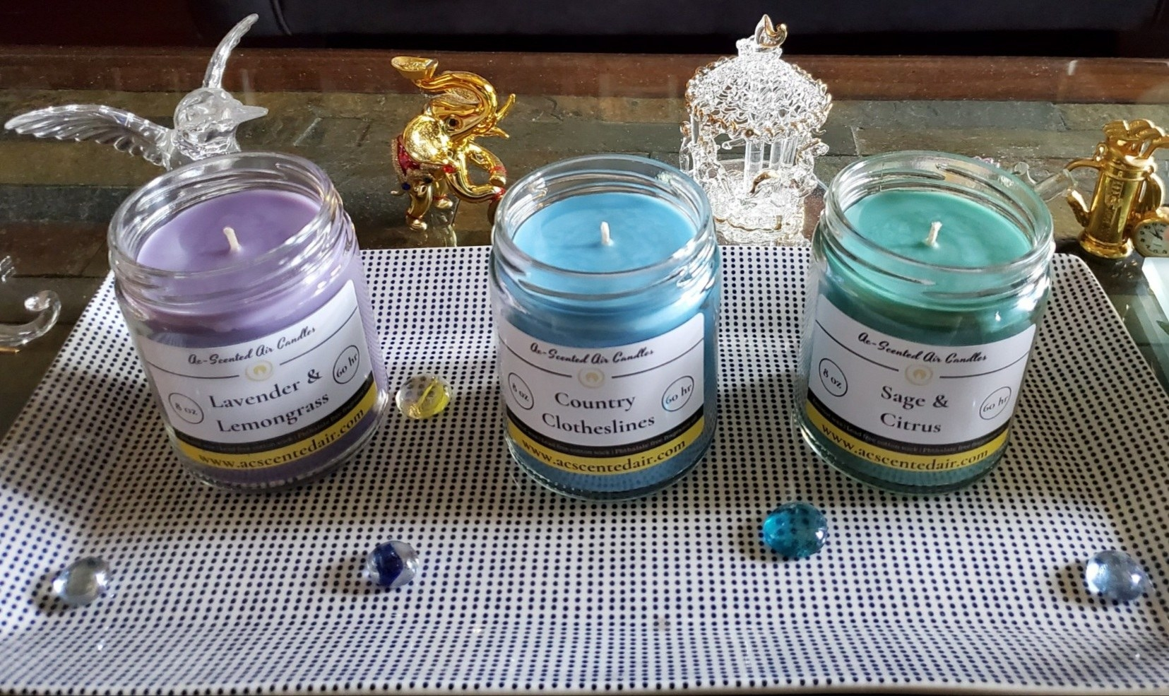 three glass candles in purple, blue, and green
