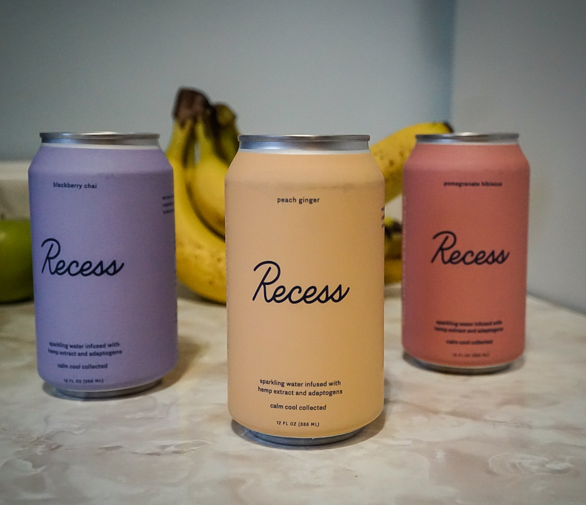 three cans of recess sparkling water on a kitchen counter