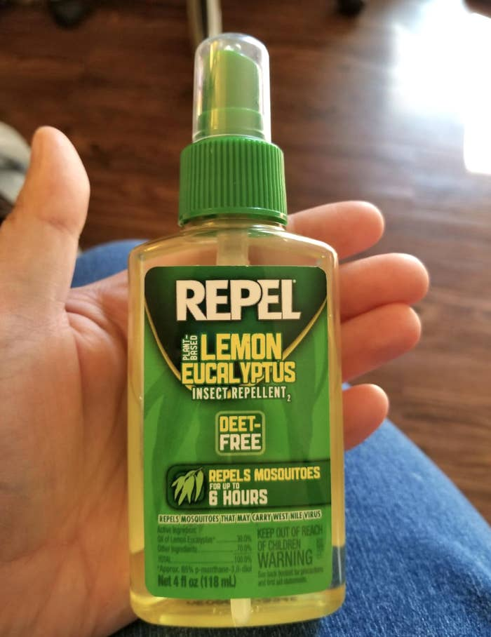 A reviewer's hand holding their bottle of insect repellant. The bottle is transparent and the liquid inside is showing (it's clear but yellow).