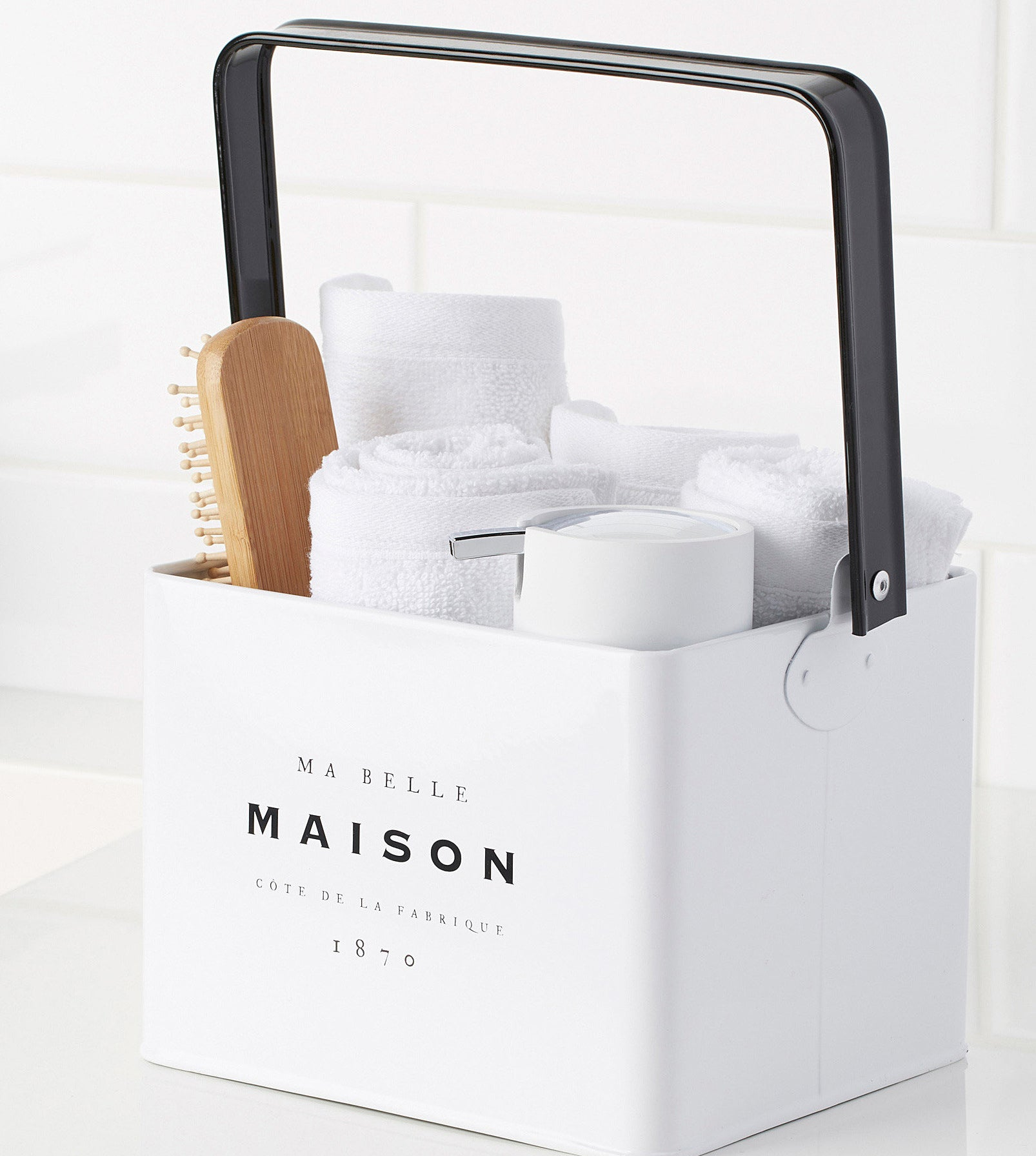 A metal basket filled with bathroom items like towels a soap dispenser and a hairbrush