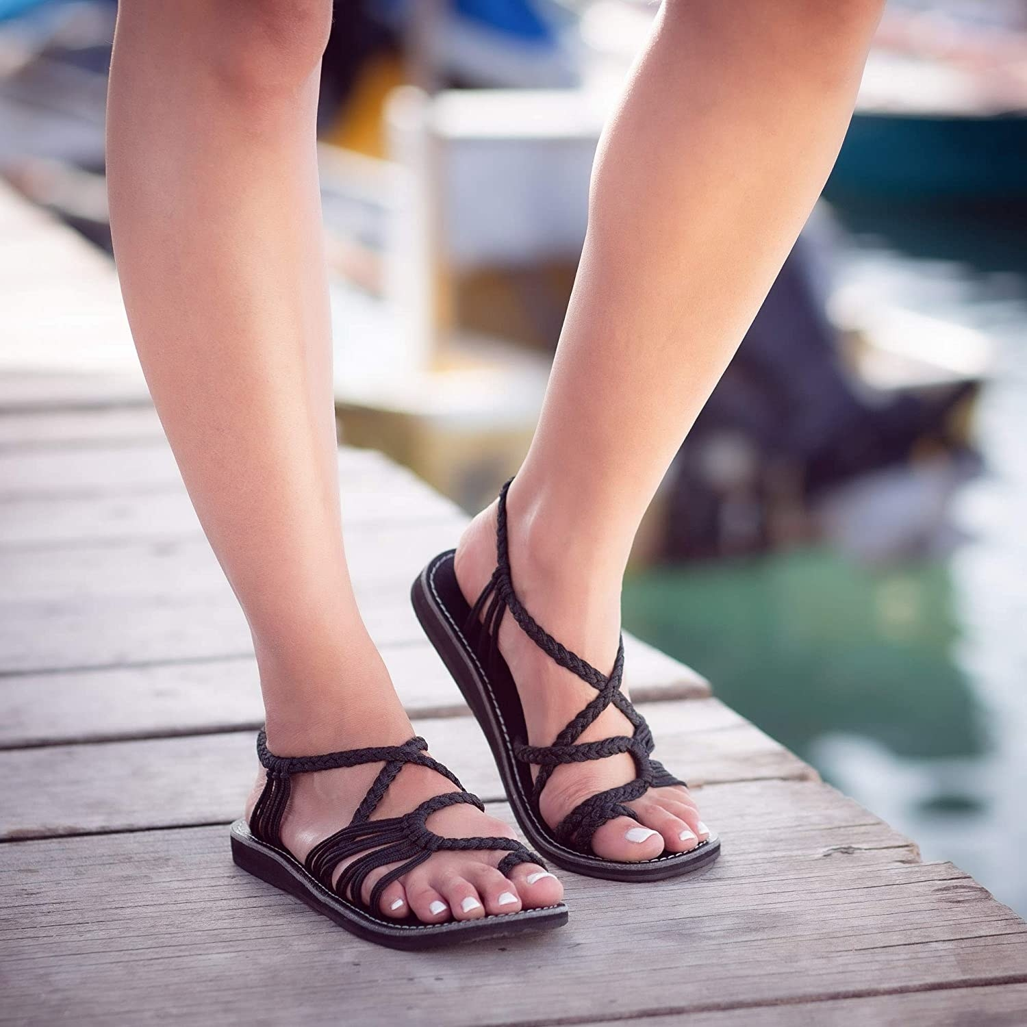 Model wearing the sandals with braided straps across the top and around the heel in black
