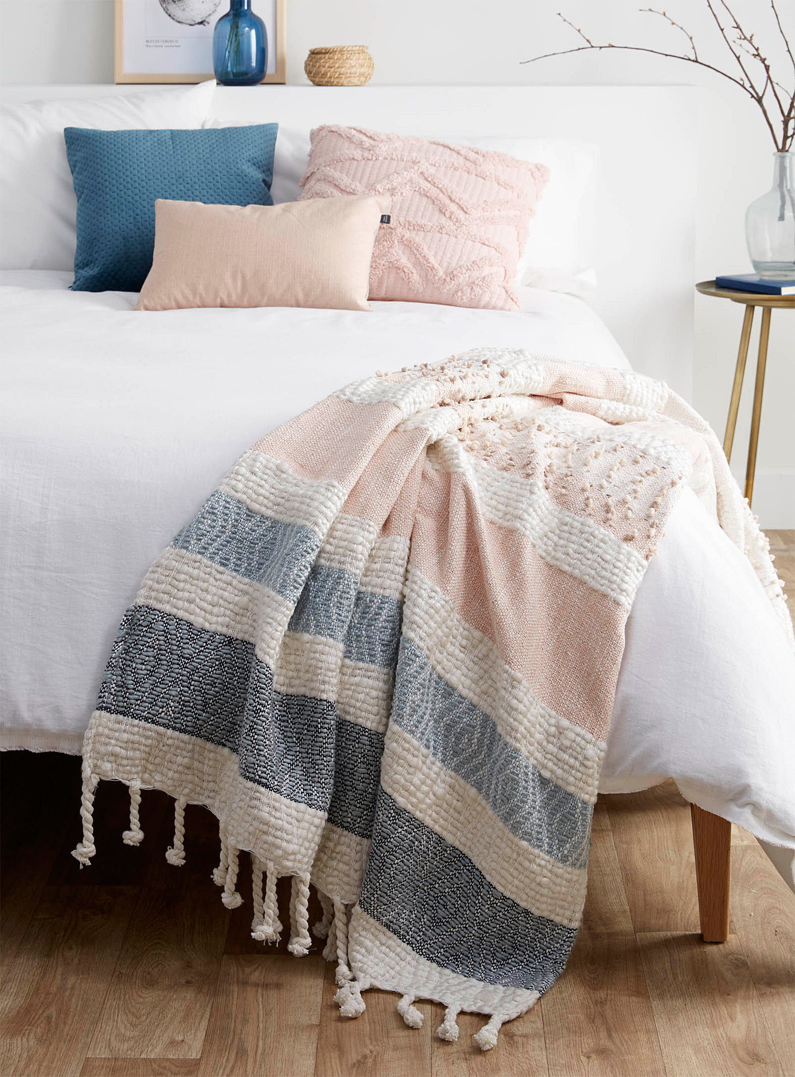 A thick throw blanket with tassels on the ends lying at the end of a bed