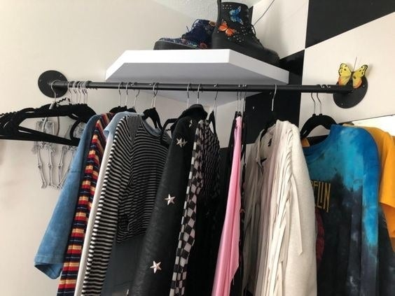 a reviewer photo of the corner clothing rod with clothes hung on it