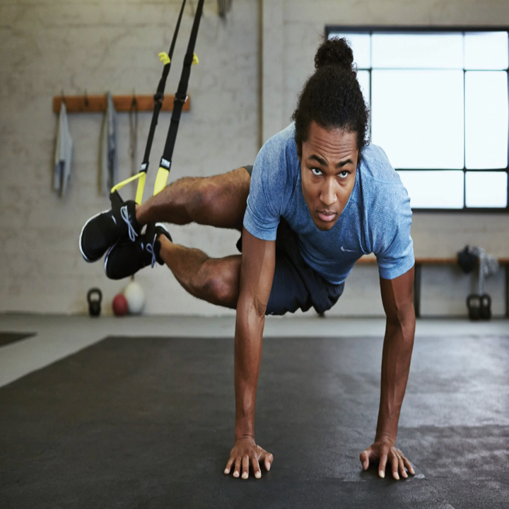 model completes pike movement with TRX Elite System in indoor gym