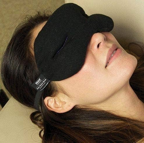 person's head resting on the arm of a chair while they wear the eye mask
