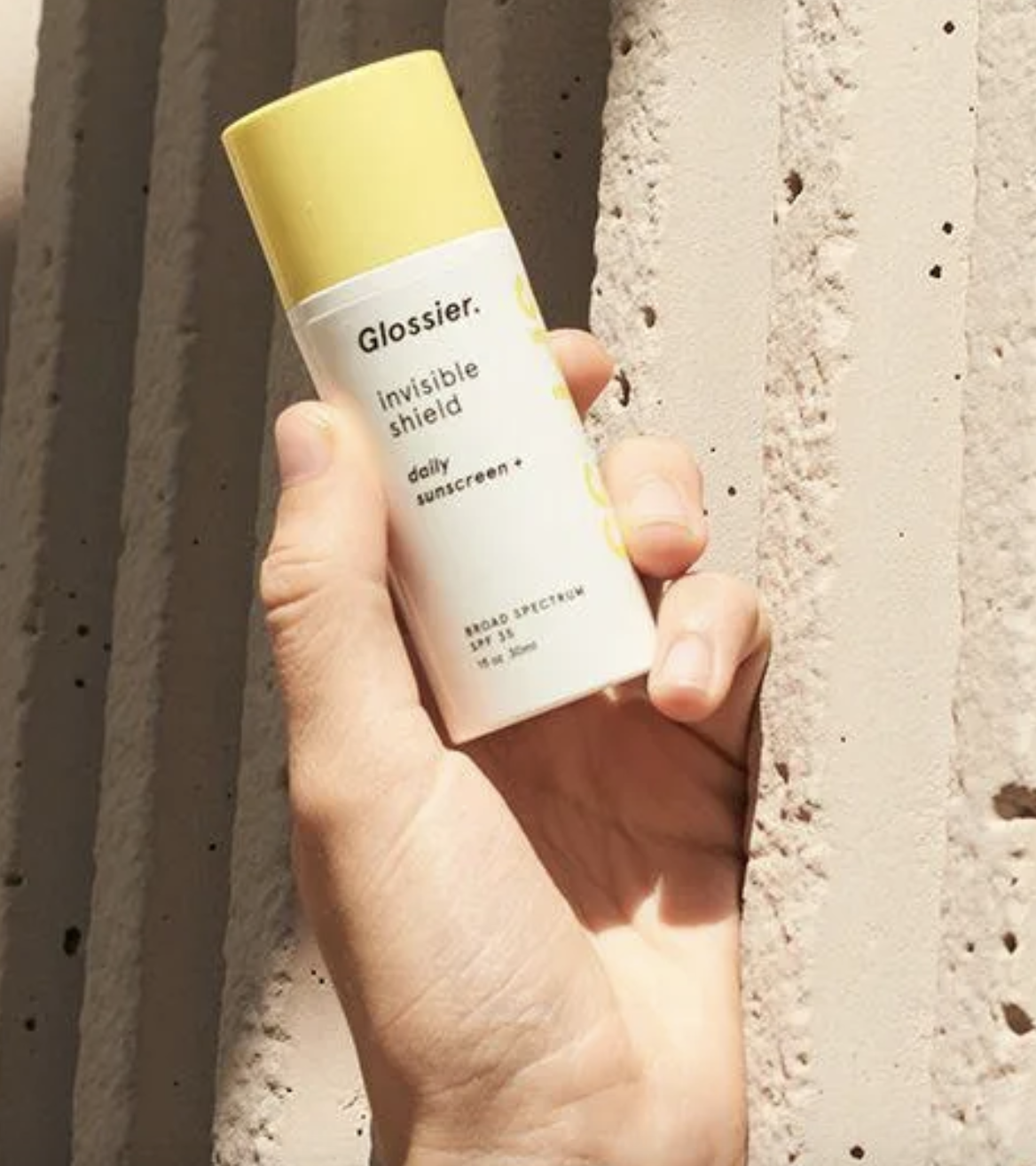 "hand holding white tube with yellow cap labeled ""glossier invisible shield"""