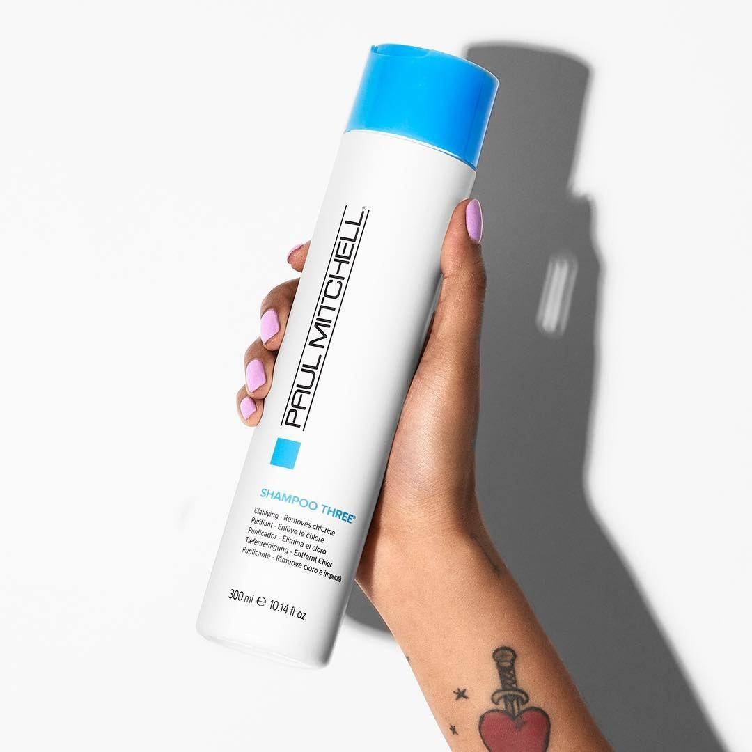 "hand holding white bottle with blue cap labeled ""Paul Mitchell"""