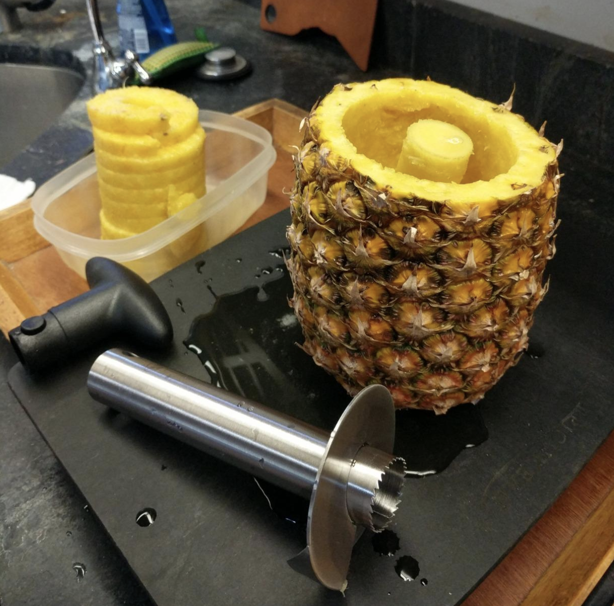 stainless steel corer next to empty pineapple with cut pineapple slices next to it