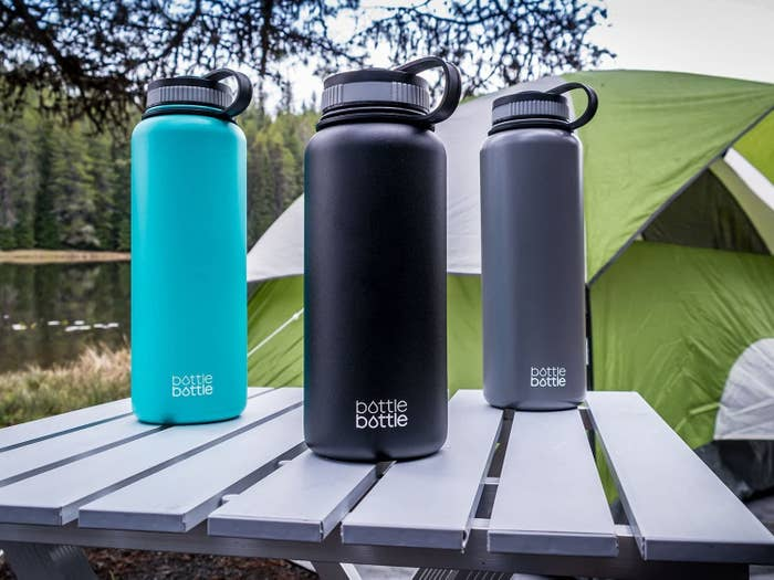 Three large stainless steel water bottles sitting on a wooden picnic table