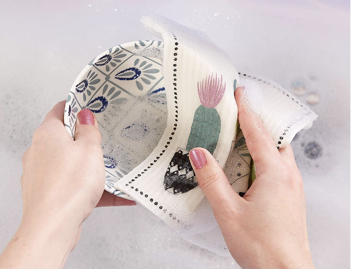 Close up of a model's hands using the dishcloth with a cacti design and dotted boarder to clean a bowl