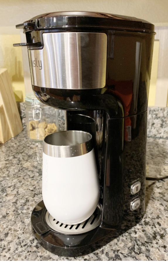 A reviewer image of the machine with a cup for coffee under it