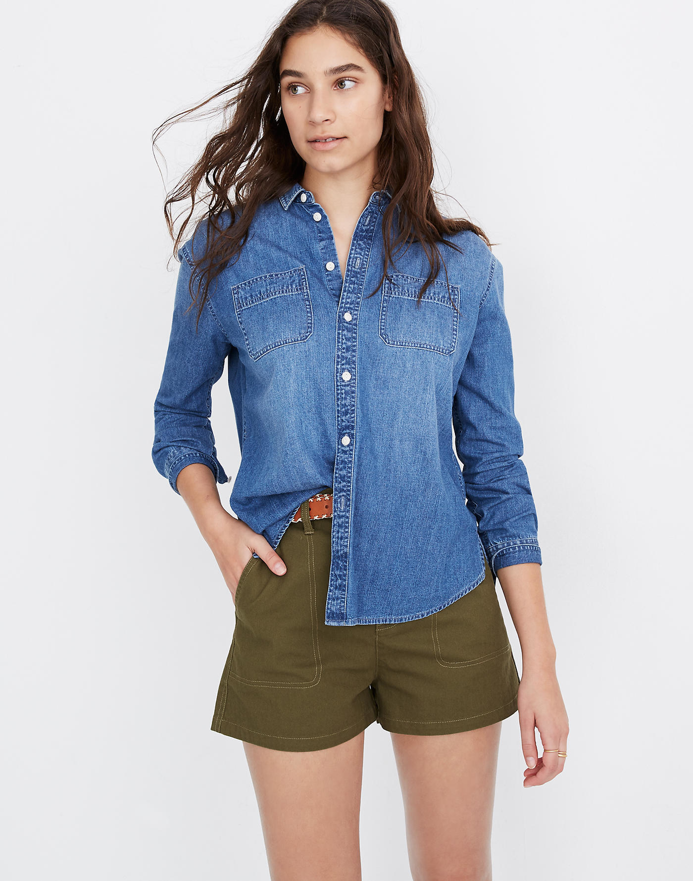 Model wearing button-down blue chambray shirt