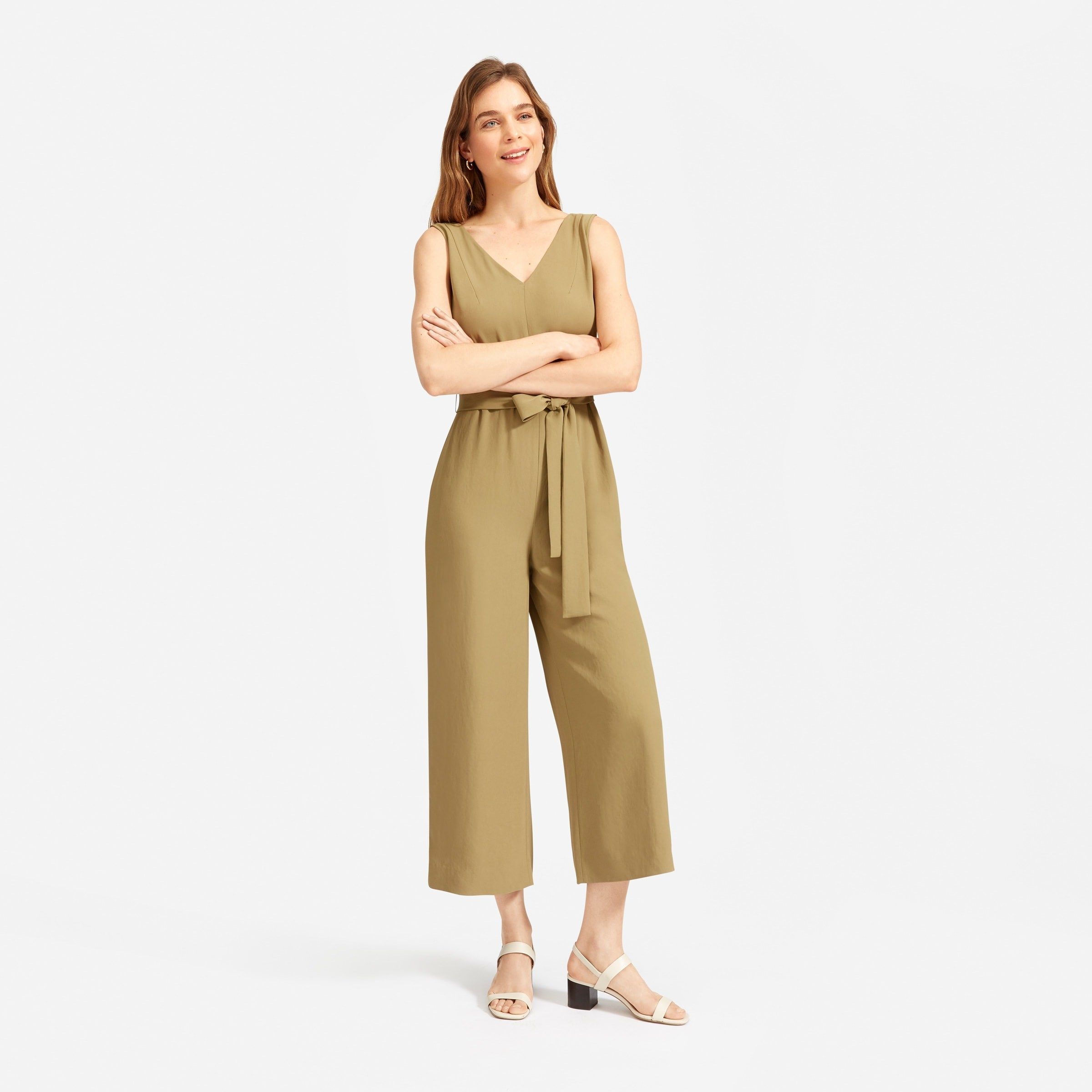 Model wearing the jumpsuit with a double-v neckline, wide legs, and a removable tie belt around the waist in olive