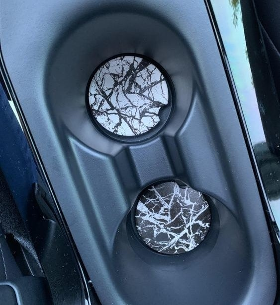 Reviewer's picture of the black and white marble car coasters in the cup holders in their car.