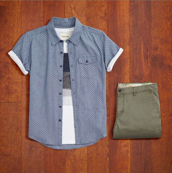 a T-shirt, button up shirt, and pair of folded shorts arranged neatly on a floor