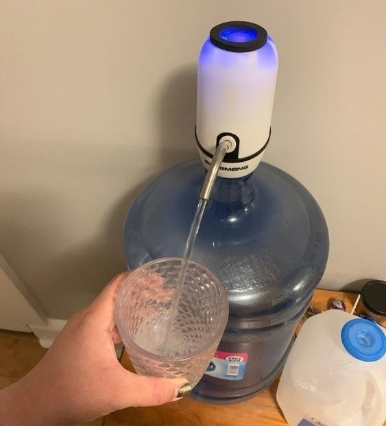 Reviewer using the dispenser to pour water from the jug, hands-free