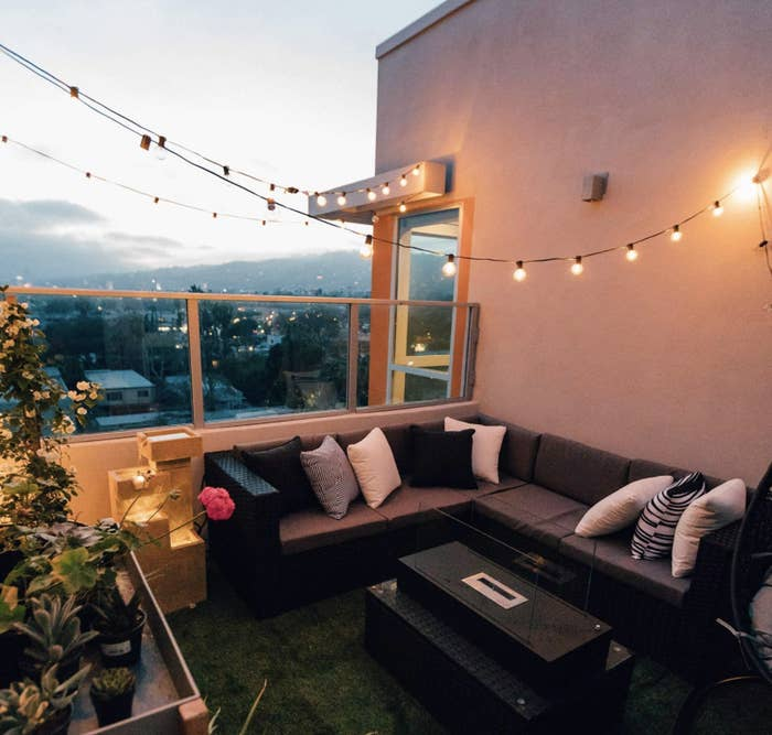 A patio at dusk with round string lights on a black wire