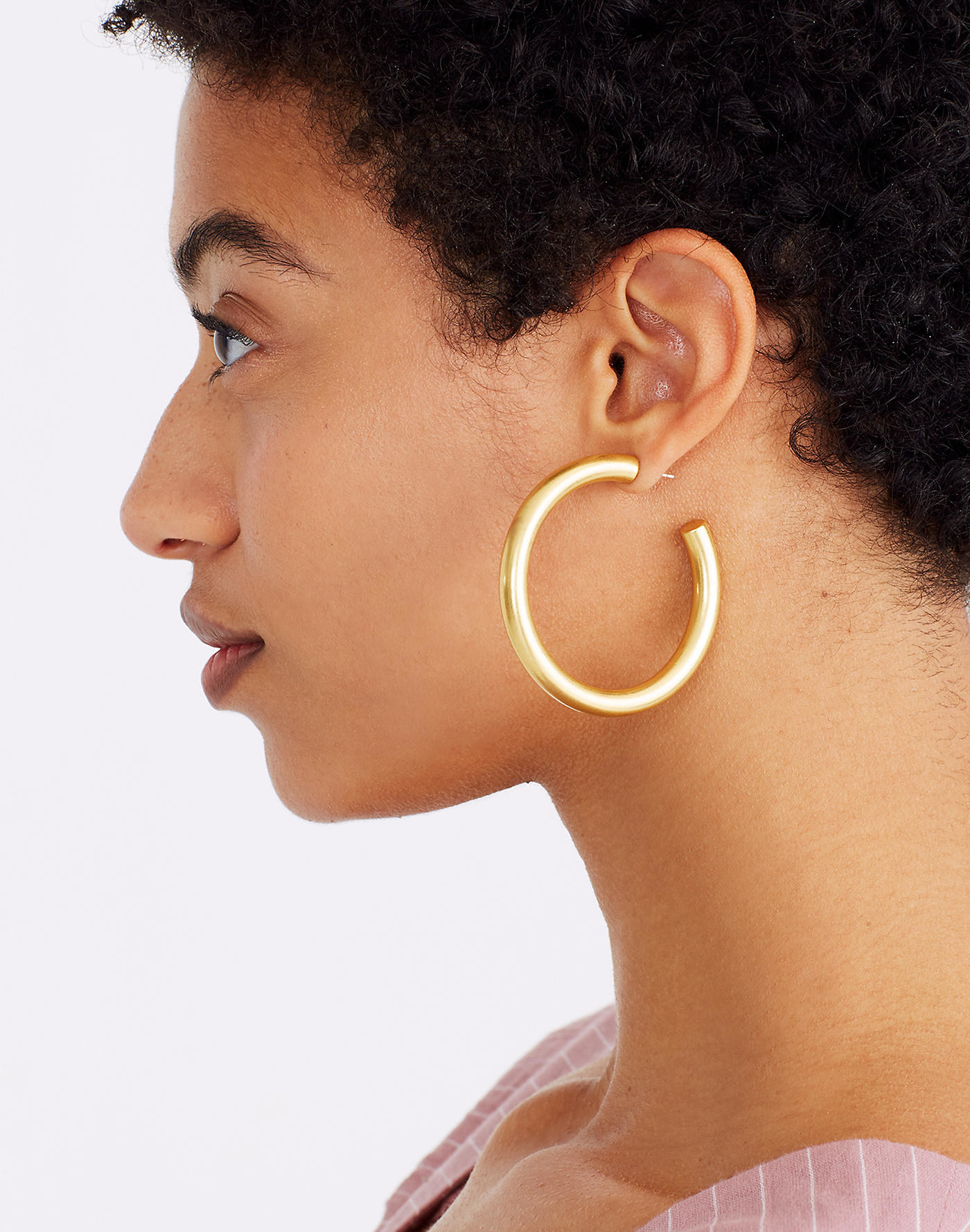 Model wearing the oversized hoops face to the side to illustrate the size, which is about the same diameter as a cup