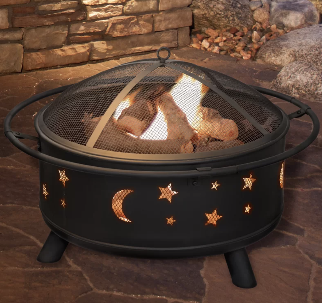 A moon and star detailed fire pit glowing at night