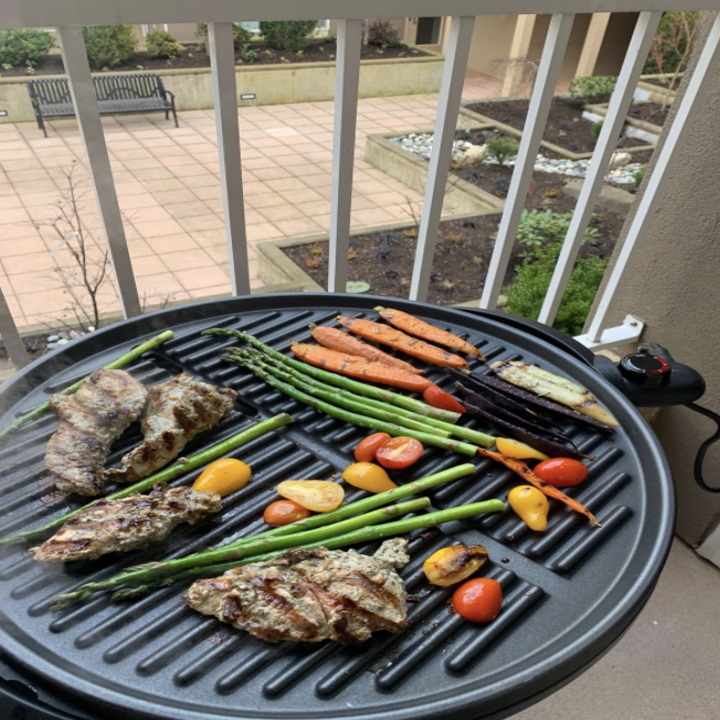 A reviewer shares a photo of the portable grill heating up meat, asparagus, and other veggies
