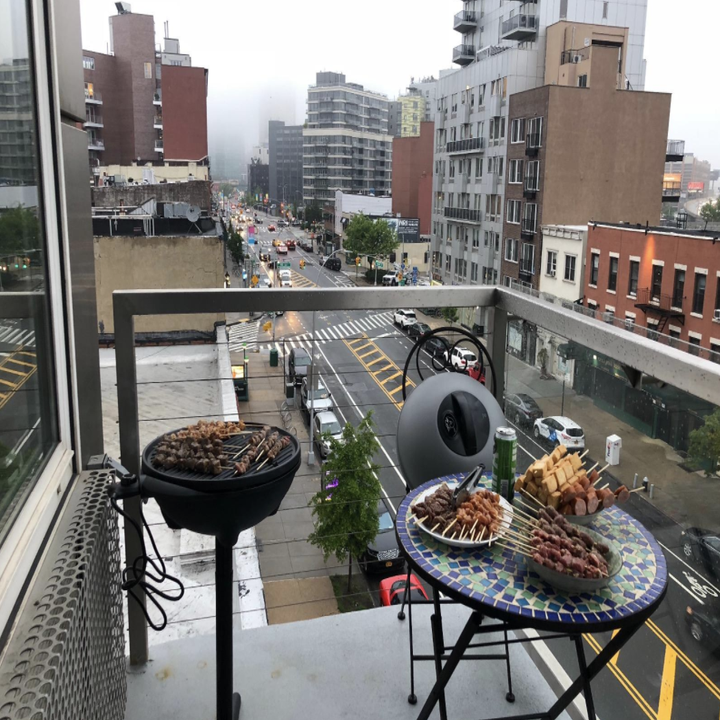 A reviewer shows the same grill on their apartment balcony, which has a tiny seating area