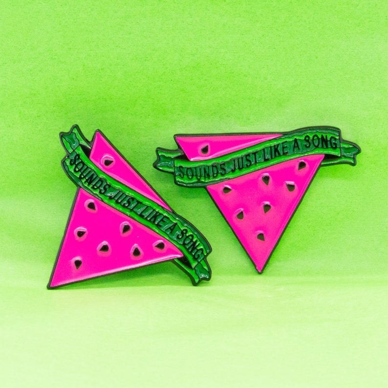 "A watermelon wedge-shaped pin with a green, watermelon-skin patterned banner across it that says ""Sounds just like a song."""