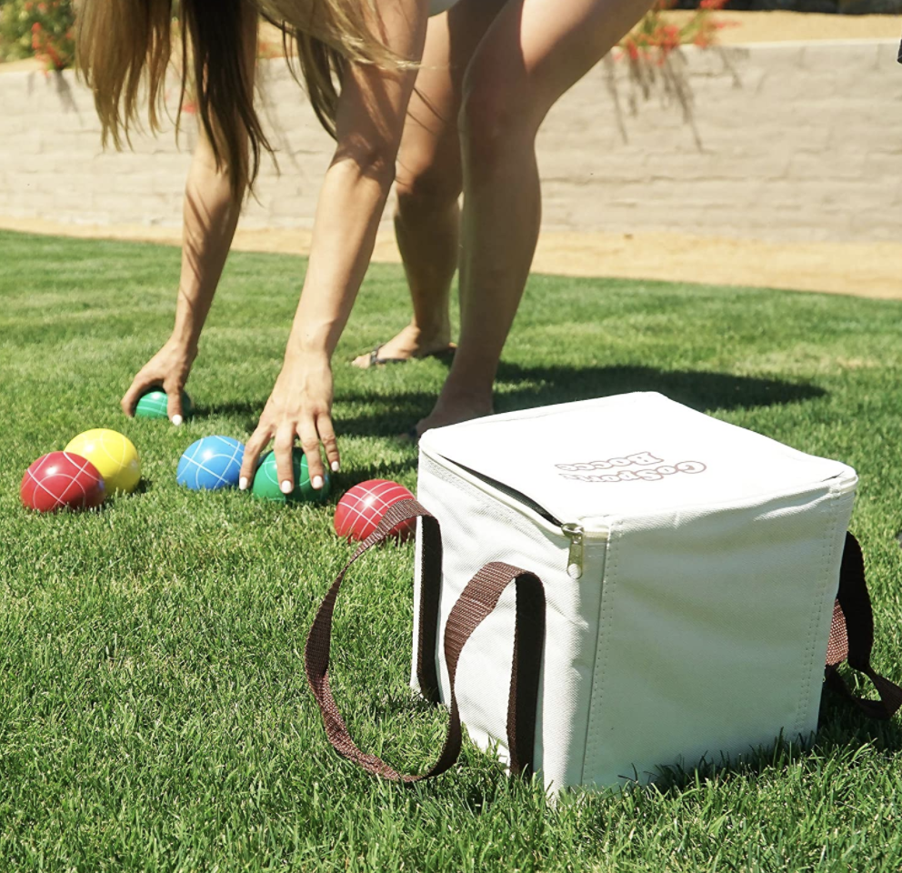 A model plays with a colorful bocce set in their yard
