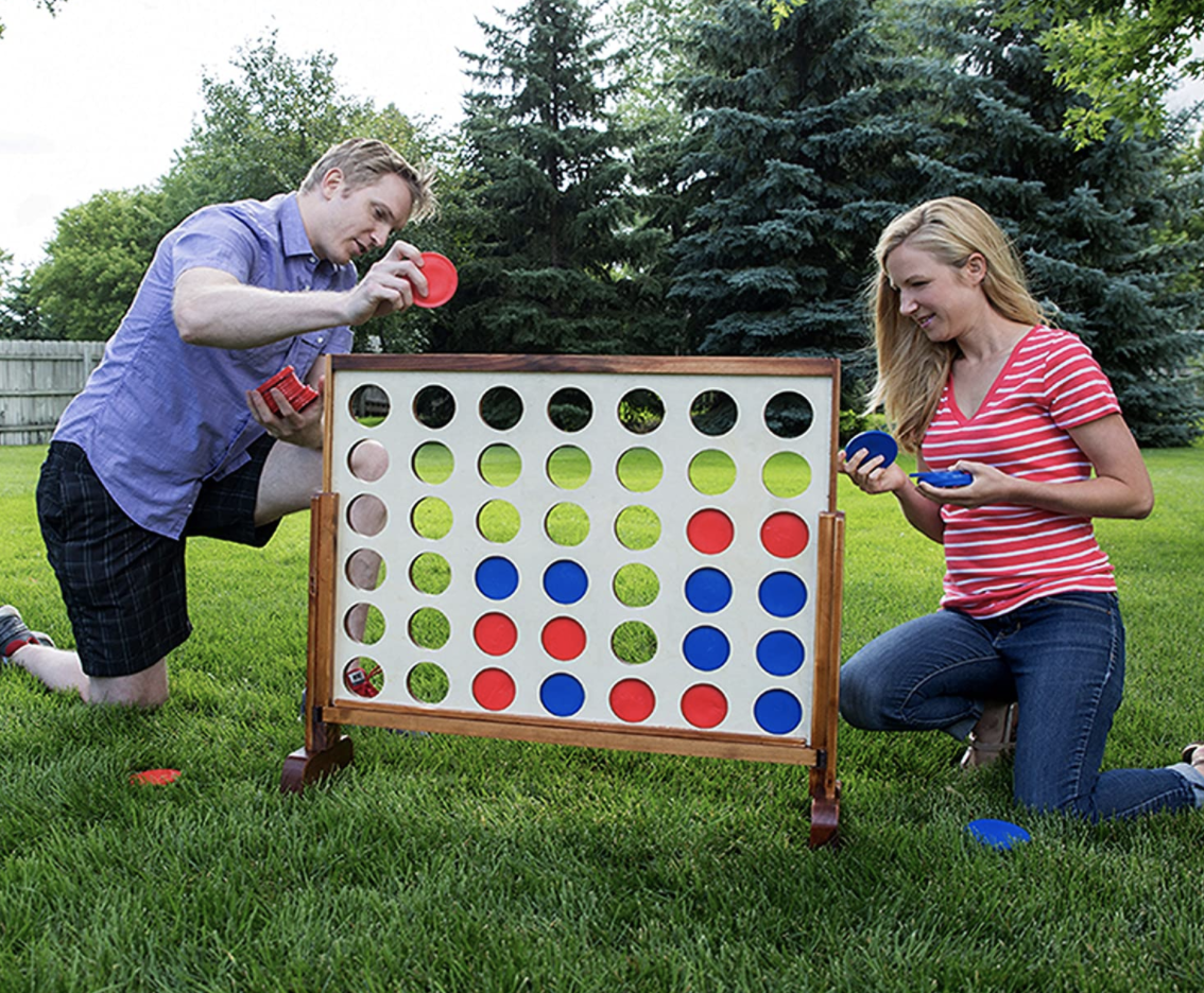 Models play with a giant 4 Connect game in their backyard