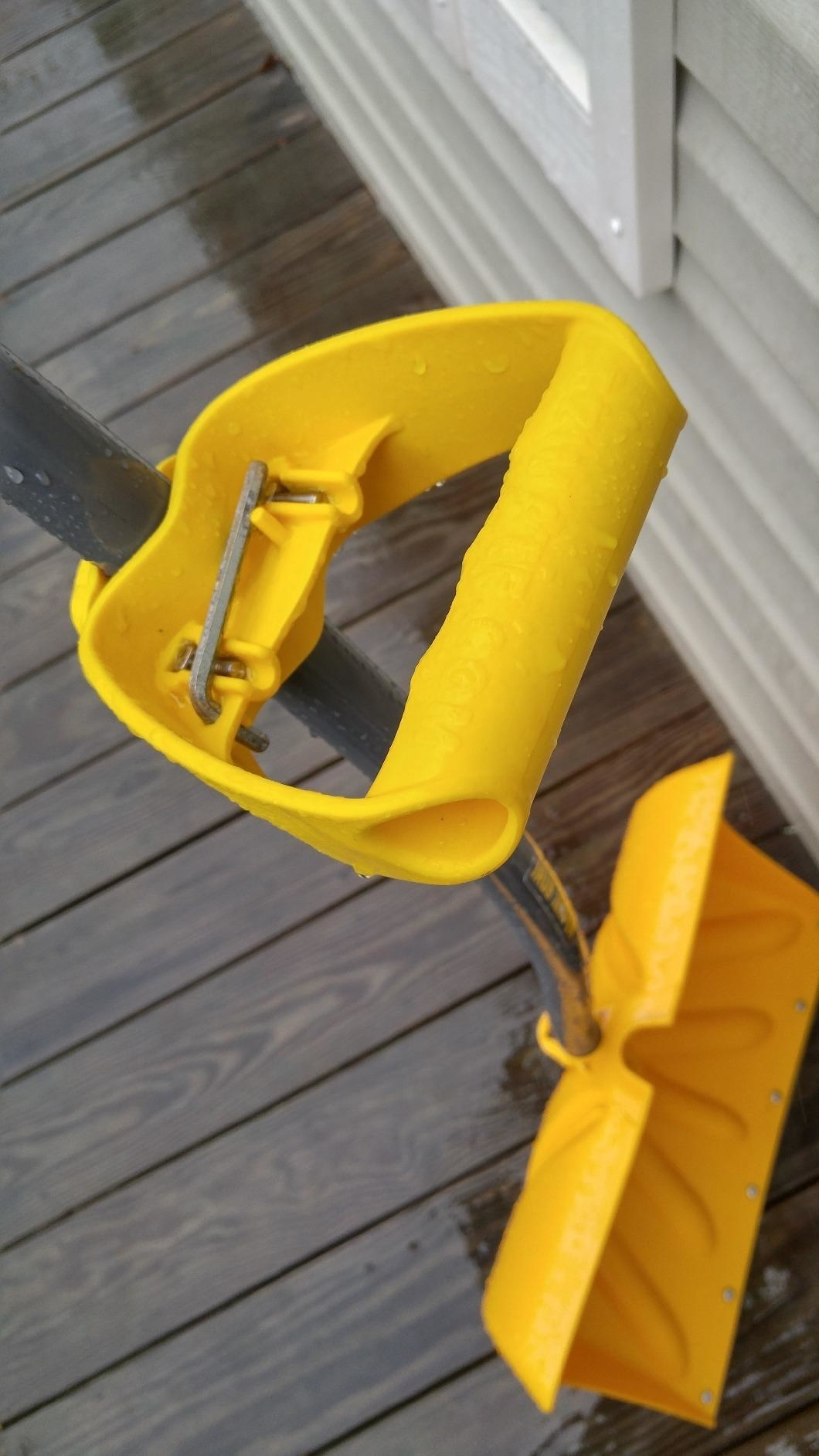 The attachment, which has a handle grip, attached to a shovel