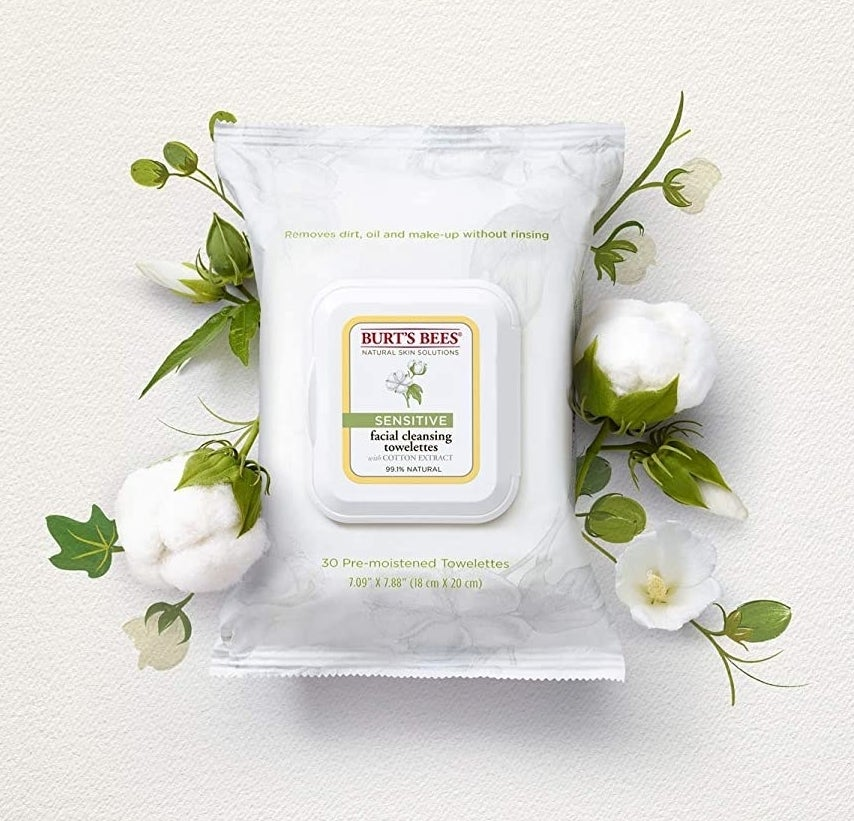 The resealable package of facial wipes is on a blank background, surrounded by cotton flowers and painted foliage