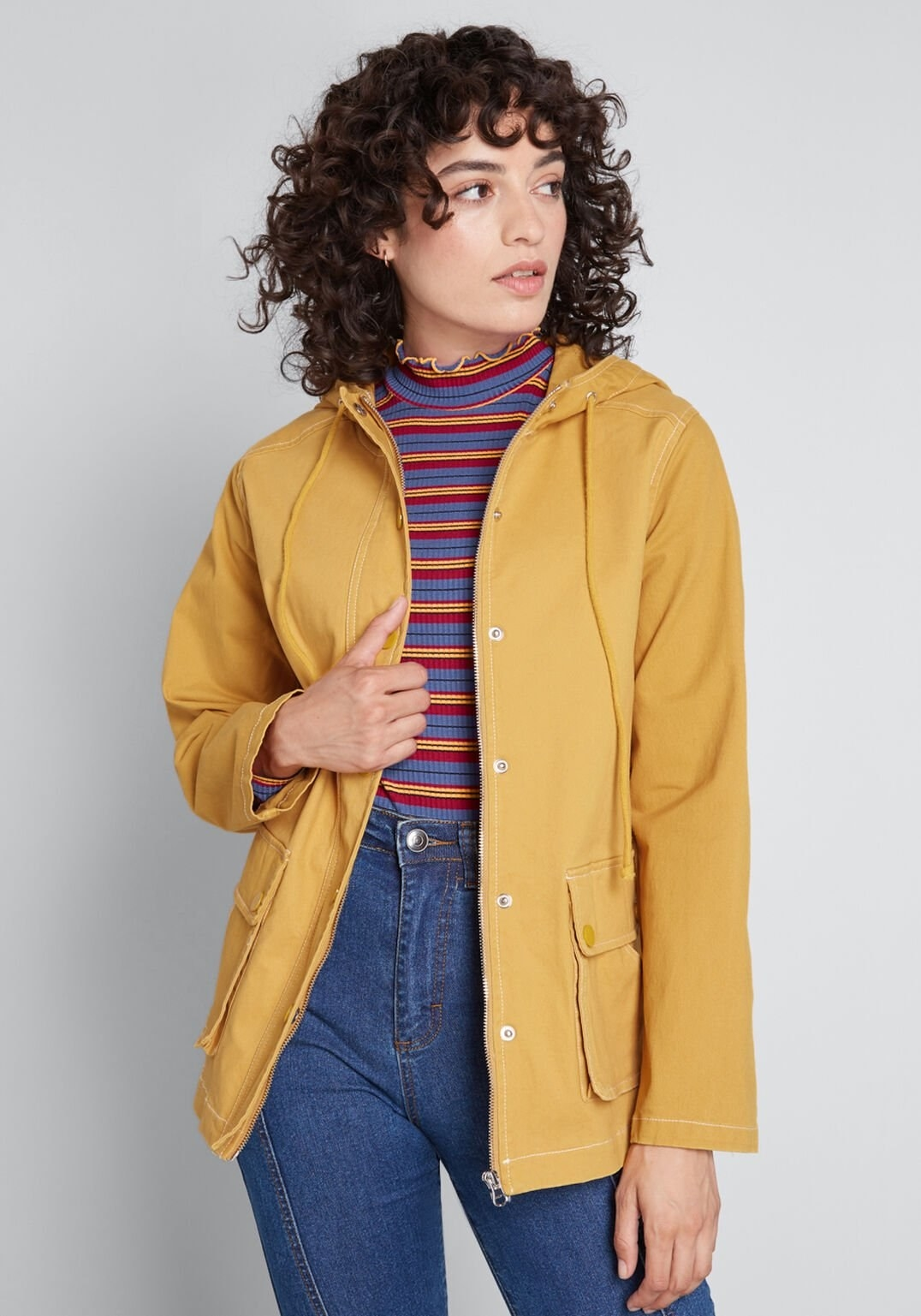 a model in the msutard-colored jacket with utility pockets, a full zipper down the middle, and draw strings hanging from the hood
