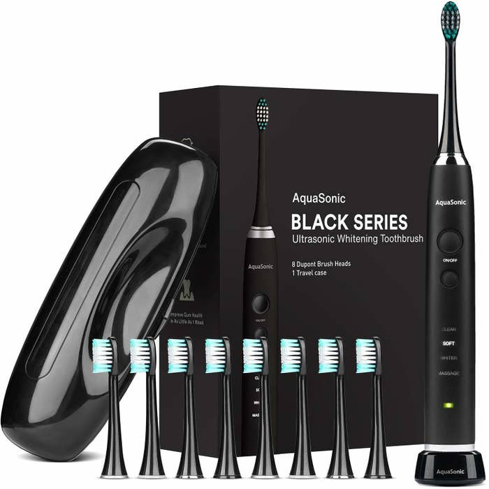 Packaging and contents of an electric toothbrush set including handle, eight heads, and case all in black
