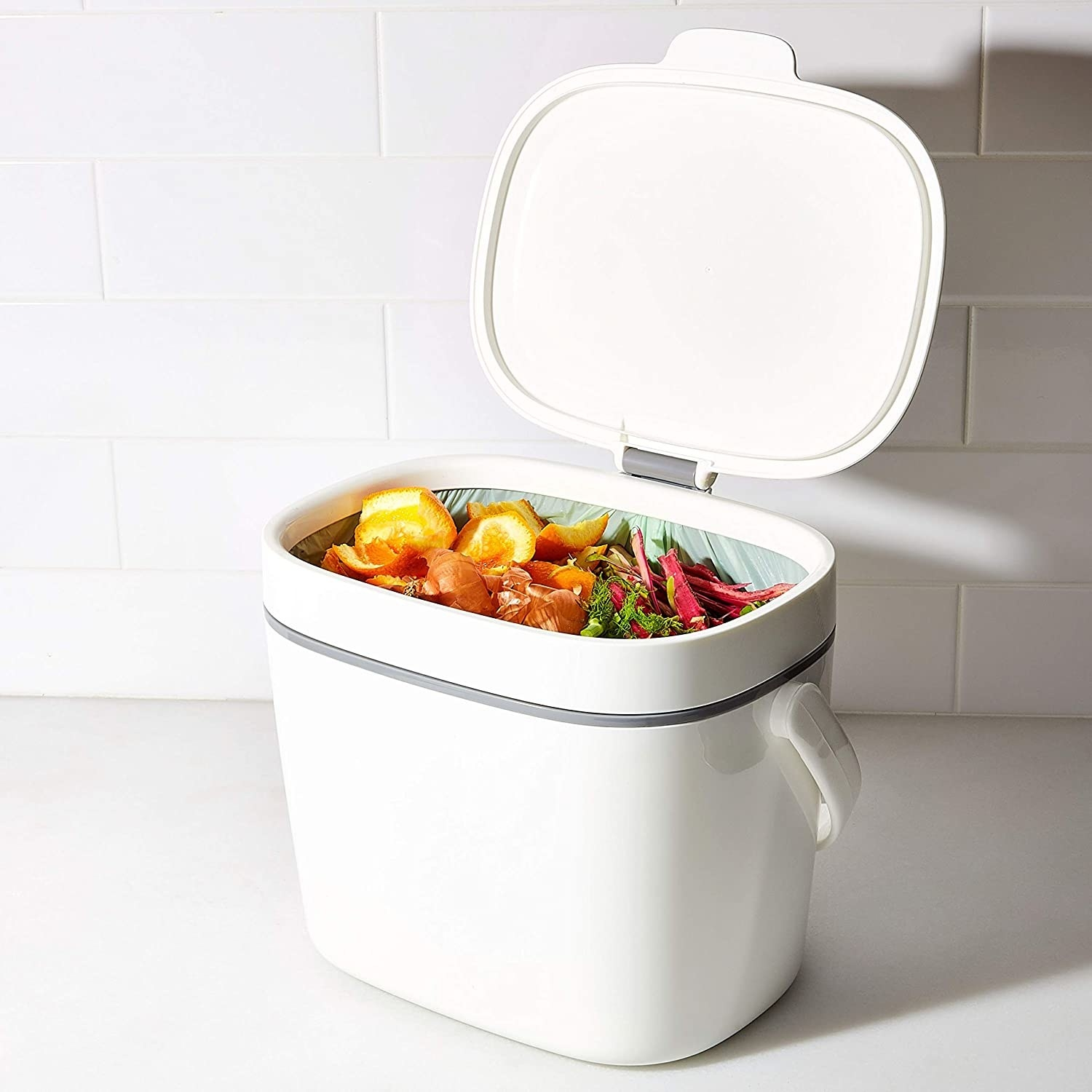 A smooth white canister with a lid, handle, and removable waste bag. It is filled with food trimmings.
