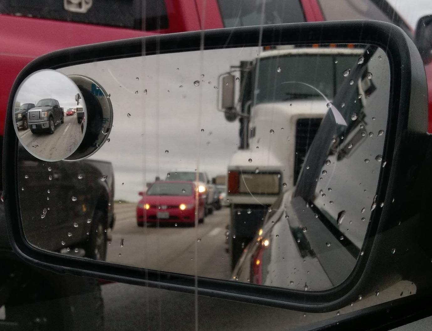 A blind spot mirror showing a wide view of the road on a highway