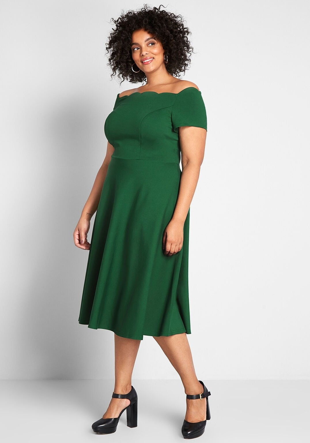 a model in the mid-length dress in emerald green