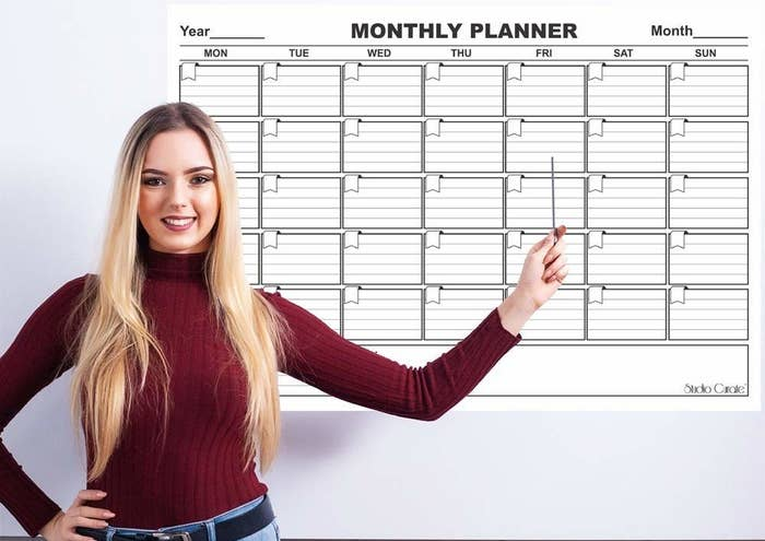 A person pointing to the monthly planner hung on a white wall