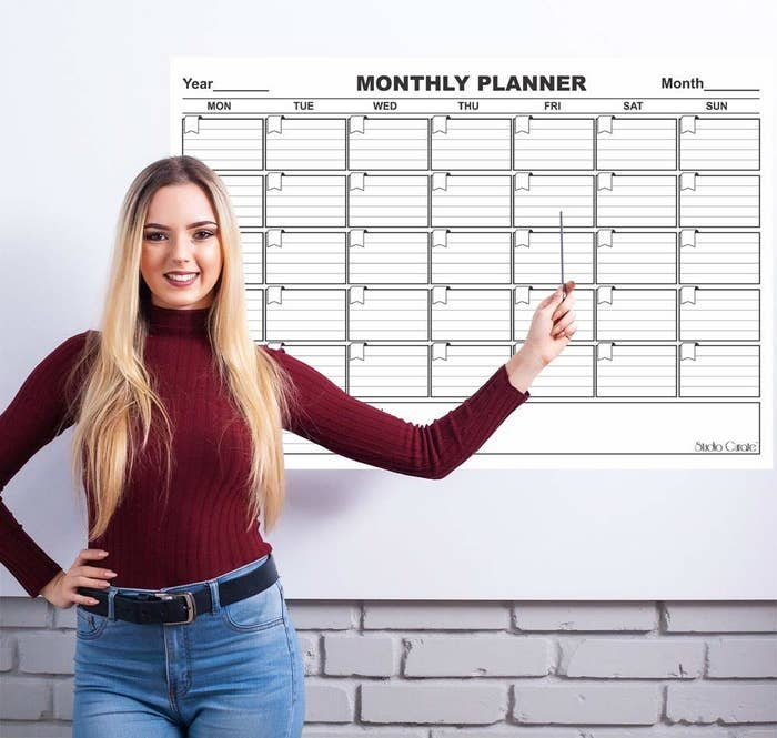A woman pointing to the monthly planner hung on a white wall