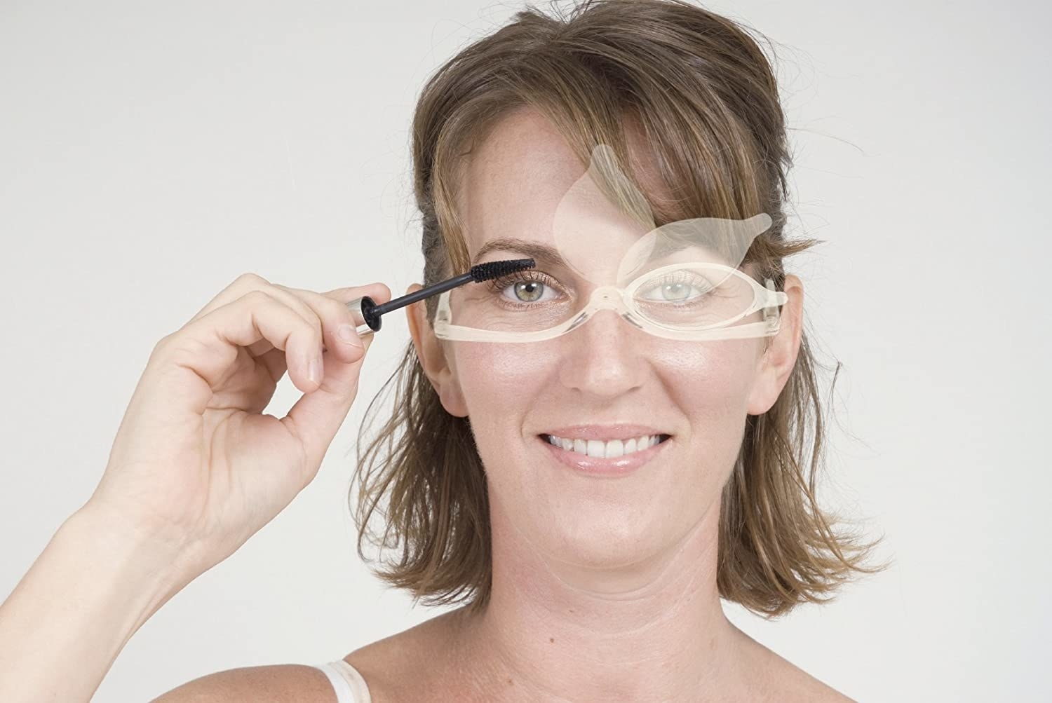 A person applies makeup while wearing the flip-lens glasses
