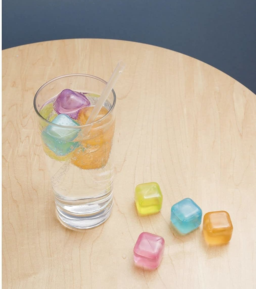 A glass is perched on a table, filled with several silicone ice cubes