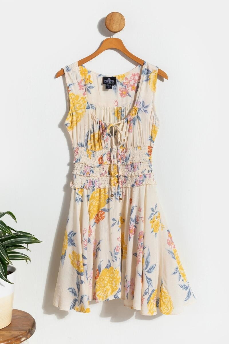 The cream dress, which has large yellow flowers on it